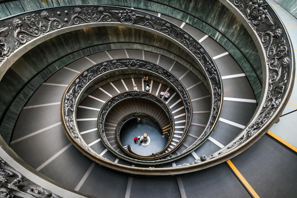 Massive spiral staircase while people climb up in the Vatican Museums