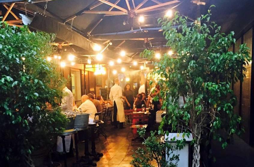 A view of a lively restaurant garden at Zanzara Rome