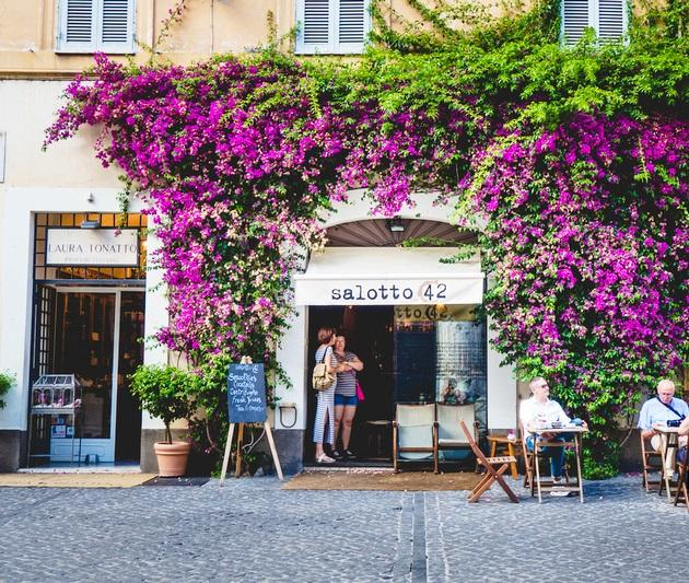 A colorful and lush entrance to Salotto 42 in Rome