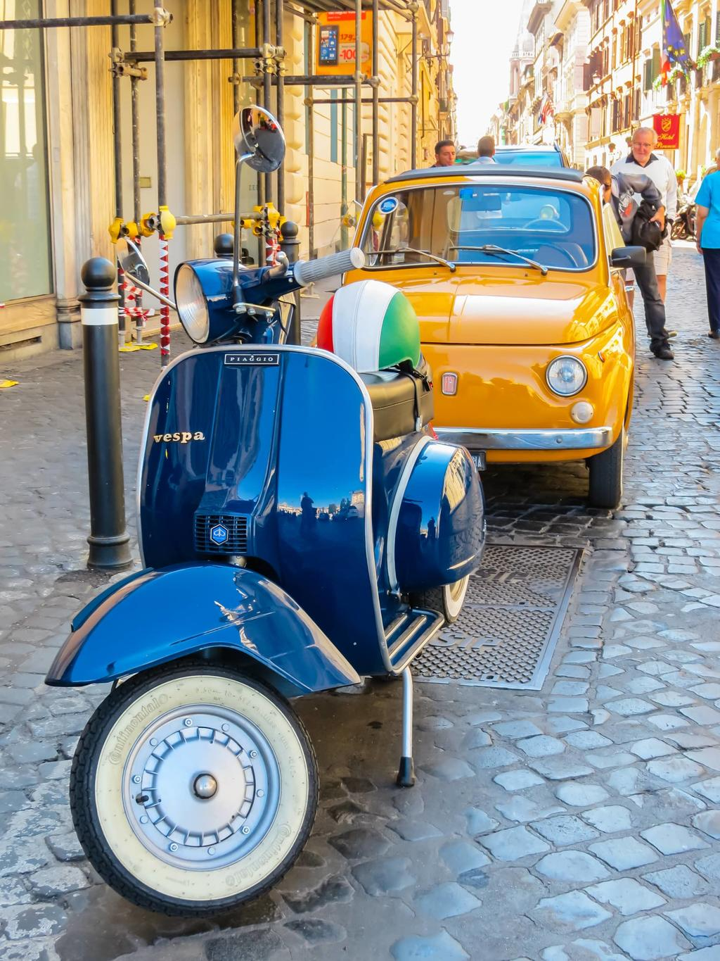 Fiat 500 and Vespa parked in Rome